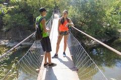 在吊桥的人为车行道的旅客旅行 活跃远足者 活跃和健康生活方式暑假 免版税库存照片