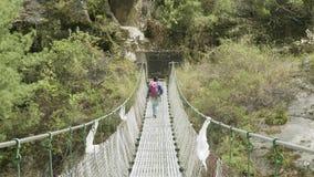 在吊桥的地方尼泊尔人步行 马纳斯卢峰电路艰苦跋涉区域 影视素材