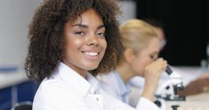 在同事专家的非裔美国人的女性科学家与做化工实验的显微镜一起使用 股票视频