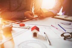 在同事之间的咨询,设计队检查图纸 免版税库存图片