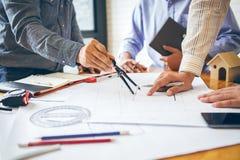 在同事之间的咨询,设计队检查图纸 免版税库存照片
