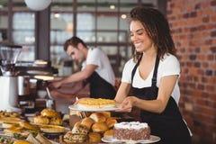 在同事前面的微笑的女服务员藏品蛋糕 免版税图库摄影