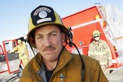 在同事和消防车前面的消防队员 免版税库存照片