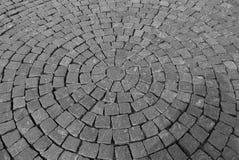 在同心圆放置的鹅卵石的灰色路面 免版税库存照片