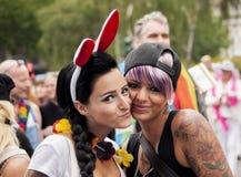 在同性恋自豪日游行期间的两个幸福女孩 库存照片