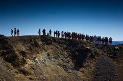 在名为卡美尼岛的火山岛上的游人 库存图片