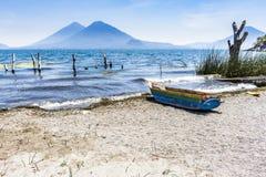 在后边海滩&火山的木小船,湖Atitlan,危地马拉 免版税库存图片