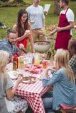 在后院享受膳食的朋友 免版税图库摄影