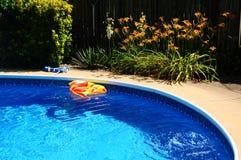 在后院游泳池的一条膨胀的玩具鱼 免版税库存照片