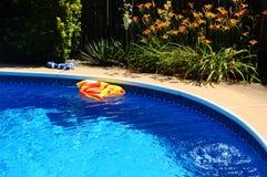 在后院游泳池的一条膨胀的玩具鱼 免版税库存图片