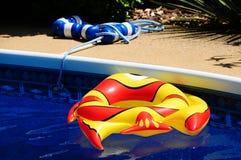 在后院游泳池的一条膨胀的玩具鱼 库存图片