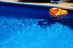 在后院游泳池的一条膨胀的玩具鱼 图库摄影