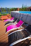 在后院游泳池的轻便折叠躺椅 库存照片