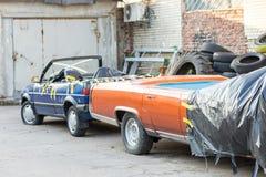 在后院的老被击毁的被盖的汽车车间 在黑帷幕下的被放弃的两用车辆在车库门附近 回收a 库存照片