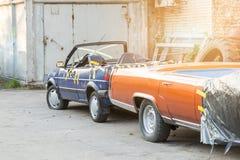 在后院的老被击毁的被盖的汽车车间 在黑帷幕下的被放弃的两用车辆在车库门附近 回收a 库存图片