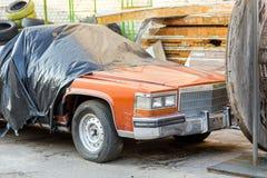 在后院的老被击毁的被盖的汽车车间 在黑帷幕下的被放弃的两用车辆在车库门附近 回收a 免版税库存照片