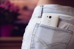 在后面口袋妇女的牛仔裤的手机在一紫色backgr 免版税库存照片