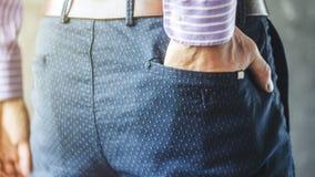 在后面口袋的人的手他时髦的长裤 免版税库存照片