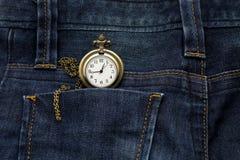 在后面口袋蓝色牛仔裤的金怀表气喘,这个图象为 免版税库存图片