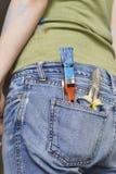 在后面牛仔布牛仔裤口袋的油漆刷和手工具 免版税库存照片