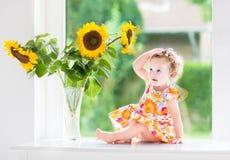 在向日葵花束旁边的逗人喜爱的卷曲女婴 免版税库存图片