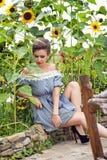 在向日葵附近的女孩在一件短的礼服14 免版税库存照片