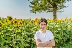 在向日葵领域的白种人男孩横穿胳膊 免版税库存照片