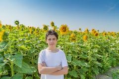 在向日葵领域的白种人男孩横穿胳膊 免版税库存图片