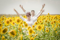在向日葵领域的美好的夫妇 库存图片
