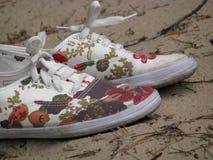 在含沙地面上的有趣的鞋子 库存图片