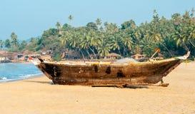 在含沙岸的老渔船。在果阿 免版税库存照片