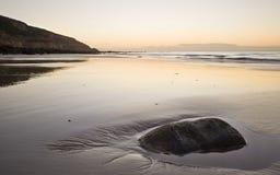 在含沙惊人的日出的海滩 免版税库存图片