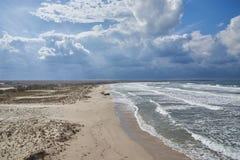 在含沙沿海的太阳光芒 免版税库存照片