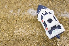 在含沙海洋岸特写镜头的玩具船在与bokeh作用的被弄脏的背景 库存照片