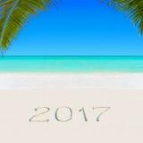 在含沙海洋热带棕榈滩的新年快乐2017年 免版税库存图片