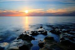 在吹的岩石珊瑚小海湾海滩的日出 库存图片