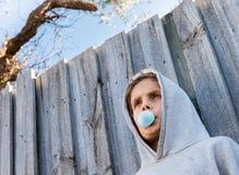 在吹蓝色泡泡糖的十几岁的男孩下角度图 库存图片