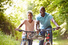 在周期乘驾的成熟非裔美国人的夫妇在乡下 免版税库存图片