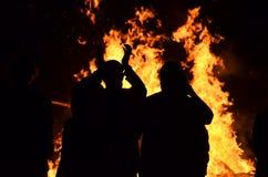 在咆哮火焰火篝火附近现出轮廓青年人 免版税库存图片
