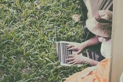 在和使用膝上型计算机的年轻人游人在帐篷在露营地 免版税图库摄影