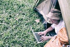 在和使用膝上型计算机的年轻人游人在帐篷在露营地 库存照片
