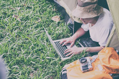 在和使用膝上型计算机的年轻人游人在帐篷在露营地 库存图片