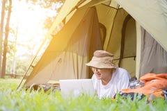 在和使用膝上型计算机的年轻人游人在帐篷在露营地 图库摄影