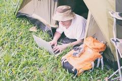 在和使用膝上型计算机的年轻人游人在帐篷在露营地 免版税库存照片