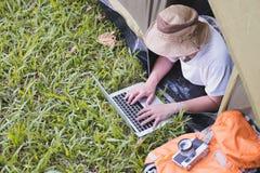 在和使用膝上型计算机的年轻人游人在帐篷在露营地 免版税库存图片