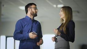 在咖啡休息期间,两个同事在办公室聊天 蓝色衬衣的人与妇女藏品沟通 股票录像