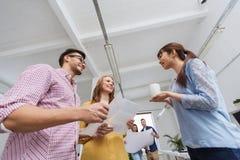 在咖啡休息的创造性的队谈话在办公室 免版税库存图片