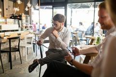 在咖啡休息的繁忙的年轻商人 库存照片