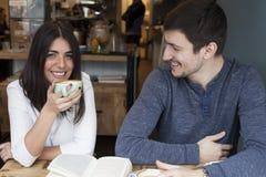 在咖啡店微笑的年轻夫妇读书 库存照片