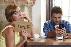 在咖啡店手机上瘾者的夫妇供以人员忽略沮丧的妇女请求帮忙 免版税库存图片